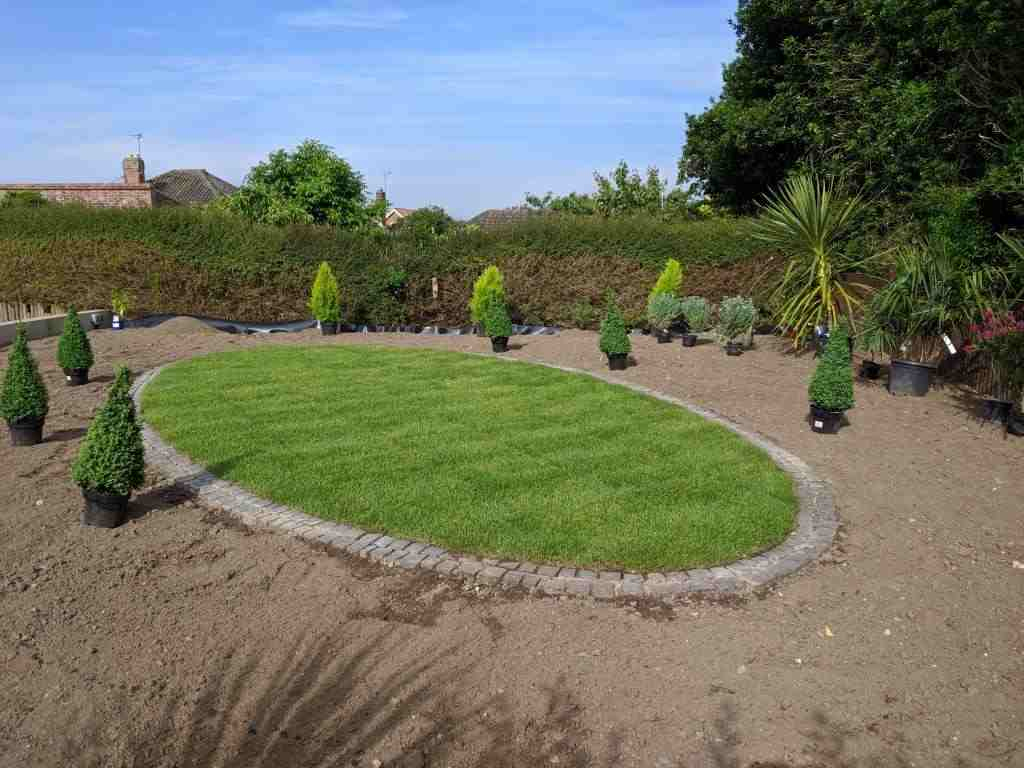 Oval lawn with paver edging and box topiary around the edge