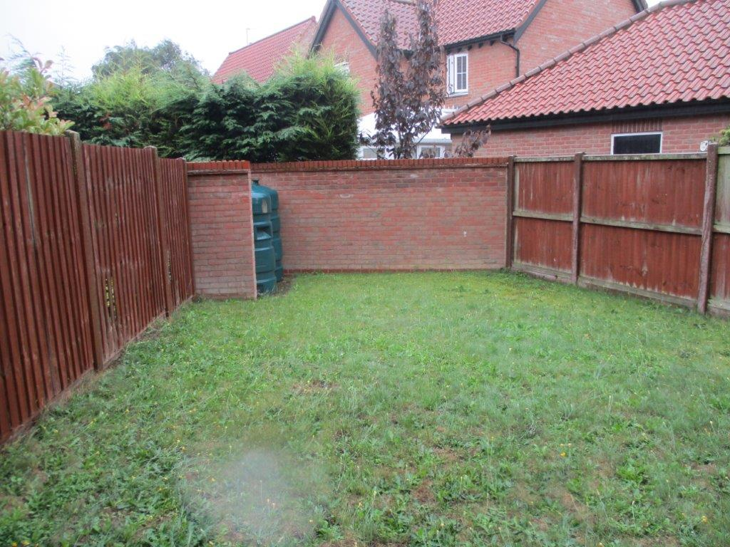 View of back garden towards oil tank before garden design and build